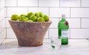 bowl of apples, bottle of liquor on counter
