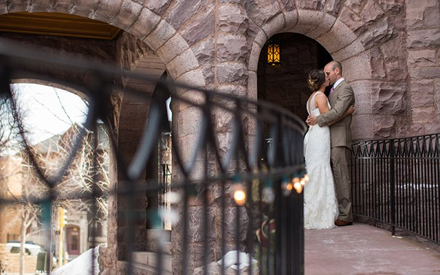 Bride and Groom kissing under an archway