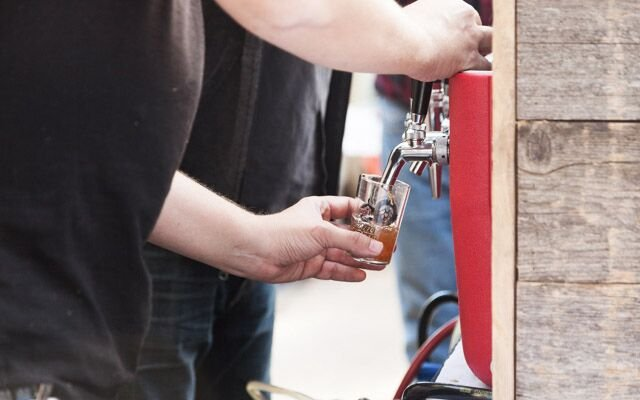 A brewer pouring a sample of beer at Mpls.St.Paul Magaz...