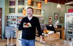 Cupcake owner Kevin VanDeraa stands inside his bakery