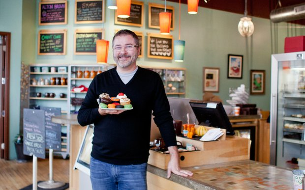 Cupcake owner Kevin VanDeraa stands inside his bakery