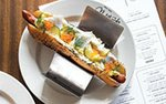 hot dog served on white plate