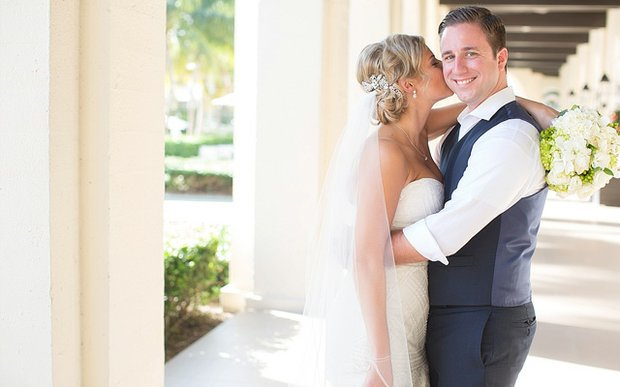 A bride kissing her groom's cheek on their wedding day