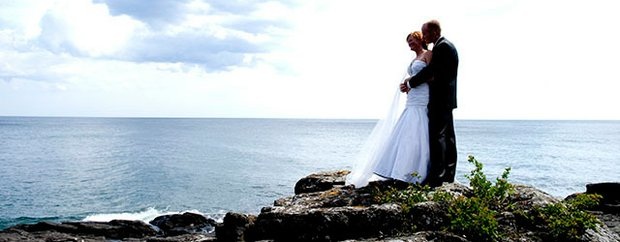 A bride and groom look out at the water at Bluefin Bay resort