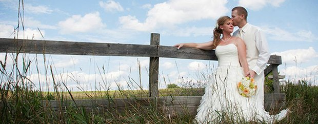 A bride and groom on their wedding day pose in front of a fence and field
