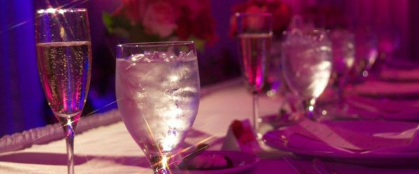 Glasses of water and champagne on a table decorated with roses