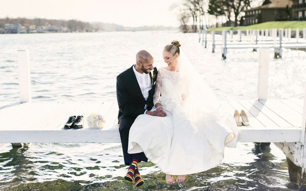A bride and groom sitting on a dock | photo by Jenna Kutcher