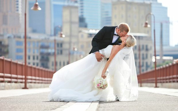 A bride and groom on the Stone Arch Bridge on their wedding day