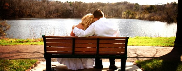 A bride and groom sitting on a bench overlooking a lake on their wedding day