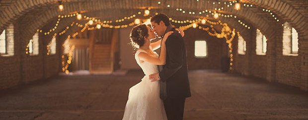 Bride and groom embrace in reception hall.