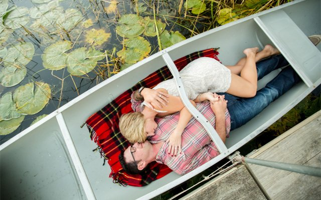 A couple laying in a canoe   Photo by Jeannine Marie Photography