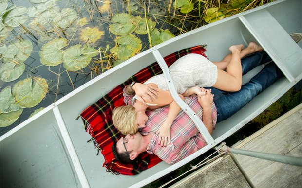 A couple laying in a canoe | Photo by Jeannine Marie Photography