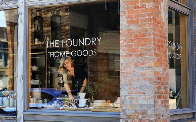 Anna Hillegass, owner of The Foundry Home Goods, stands in the store window