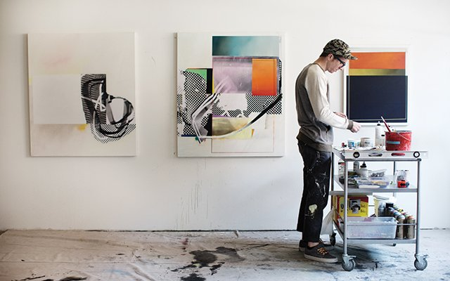 Artist working with paint, paintings hanging on the wall