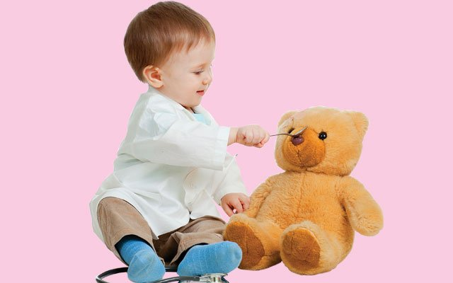 baby dressed as a doctor playing with a teddy bear
