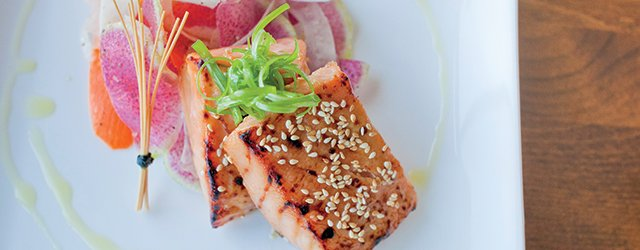 two pieces of grilled salmon on a decorated plate