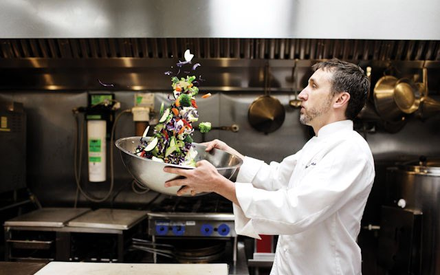 Restaurant consultant, Pat Weber, tosses a salad in a kitchen