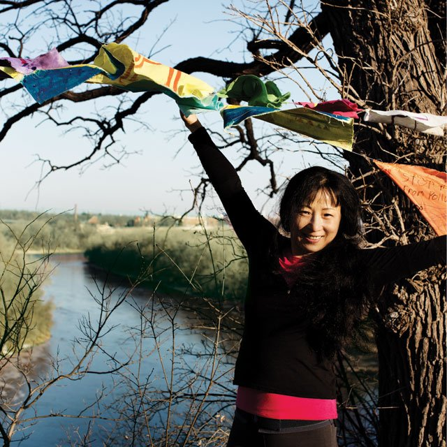 Wang Ping on the Mississippi River with her prayer flags