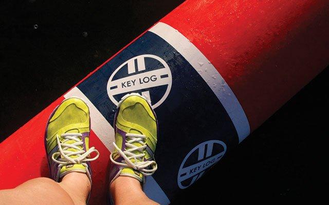 Abby Hoeschler's feet on a rolling log