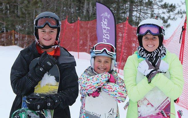 Three children with snowboards