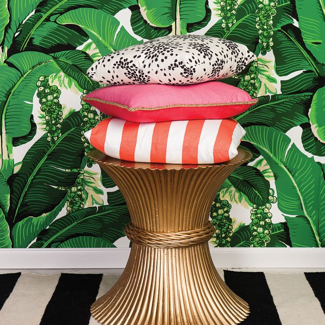 colorful throw pillows on a table with green floral wallpaper in background