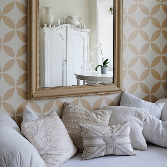 A room with gold wallpaper and white throw pillows