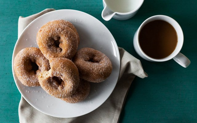 A plate of doughnuts and a cup of coffee