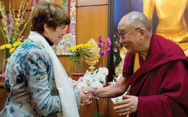 Penny George shaking hands with the Dalai Lama at his home.