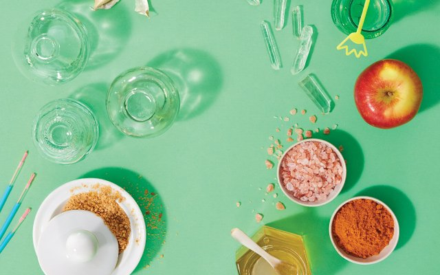 overhead shot of apple, honey, turmeric, and other items on green background