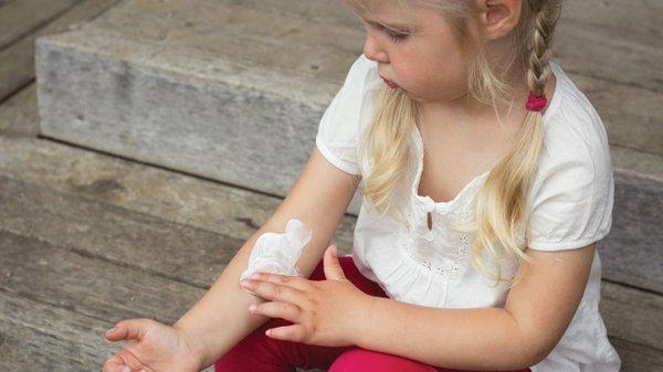 Little girl holding bandage on her arm