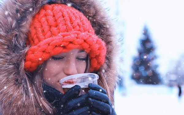 Woman drinking beer on a cold day