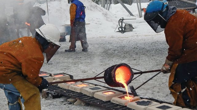 Molten iron being poured into molds to make sculptures