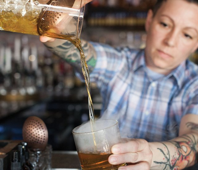 Bourbon Butcher Kitchen and Bar bartender pours a glass of whiskey
