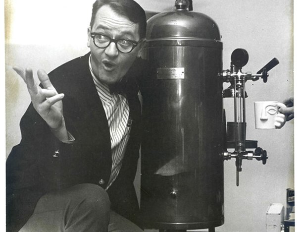 Dudley Riggs posing with the first espresso machine in the Midwest