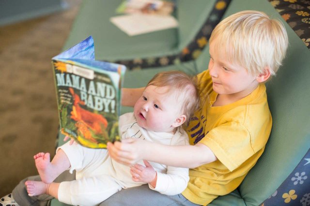 Two children read a book at Hennepin County Library