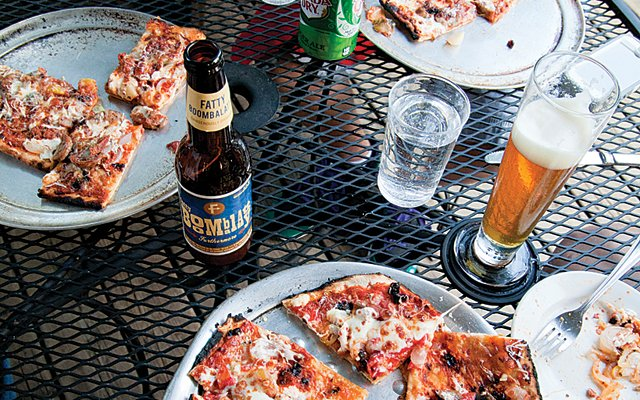 An outdoor table of pizza and beer at Chef Shack in Bay City