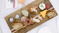 sandwich board with bread and assorted meats and cheeses