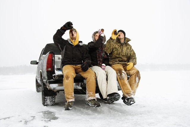 Three people drinking beer outside in winter.