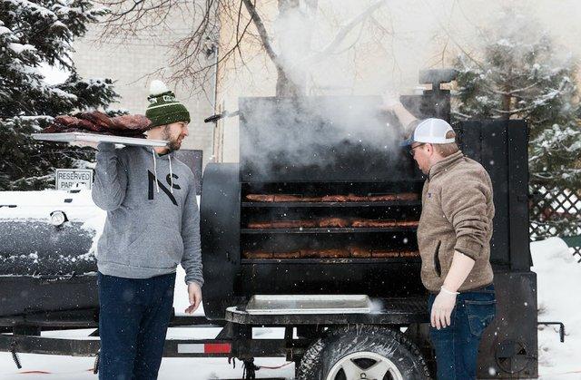 Two men smoking meat in a smoker