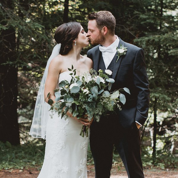 Bride holding green bouquet and kissing groom.