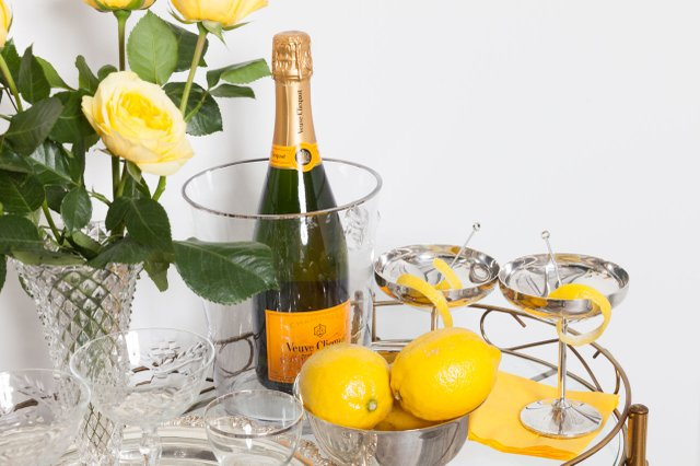 bar cart with champagne, yellow roses, lemons, and glassware