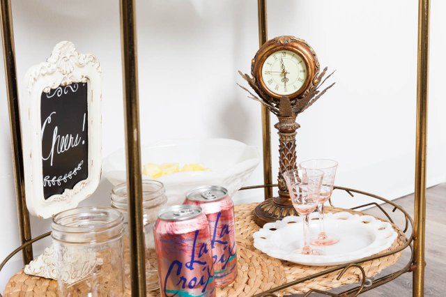 bar cart with antique clock, pink glassware, and white dishes