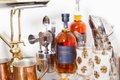 bar cart with bar utensils, glasses and bottle of liquor