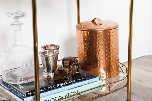 Bar cart with gold ice bucket, glass decanter and shot glasses