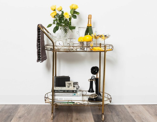 bar cart with champagne, yellow roses, lemons and books