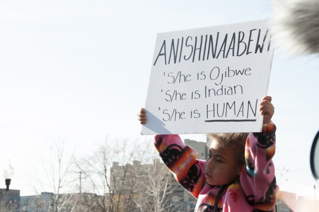A child holds up a sign at a protest in this still from Dodging Bullets