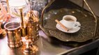 espresso in white cup on gold tray