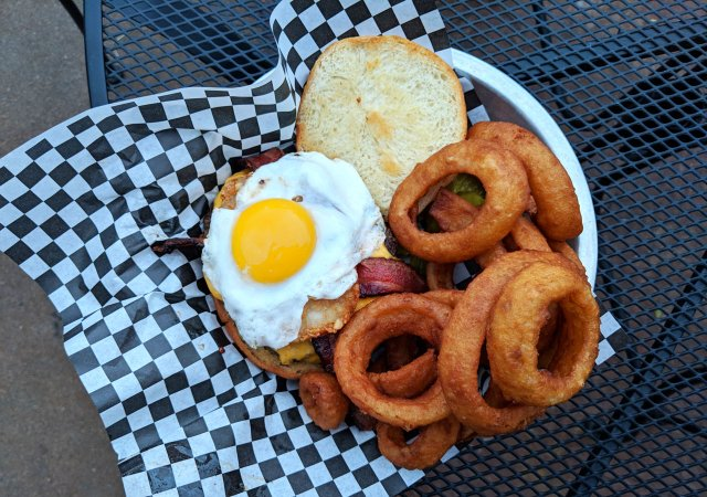 Cheeseburger with egg and onion rings from Surfside Bar and Grill