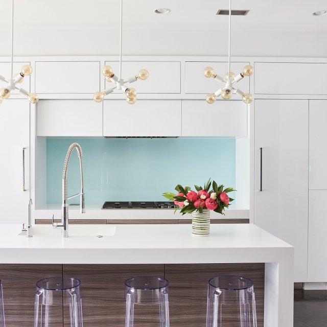 Kitchen with white cabinets and Tiffany blue backsplash