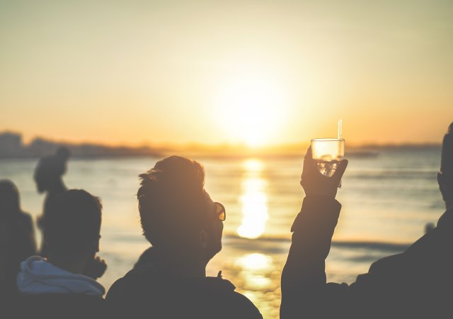 Guy holding up a drink at sunset.